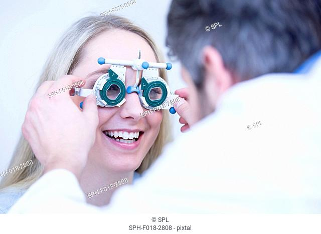 Optometrist performing eye test of young woman