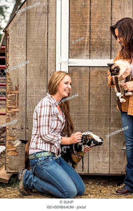 Two women on farm, holding cat and stroking goat, smiling