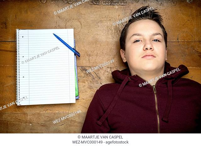 Portrait of serious looking teenage boy lying beside a notebook on wooden floor