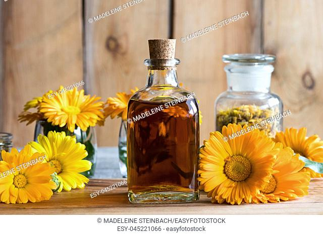 A bottle of calendula (marigold) tincture, with orange and yellow calendula flowers