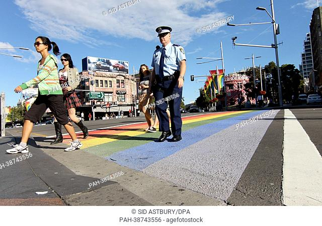 Pedestrians and a police officer cross a street via a rainbow-colored crosswalk in Sydney, Germany, 07 April 2013. Several activists painted colorfull...