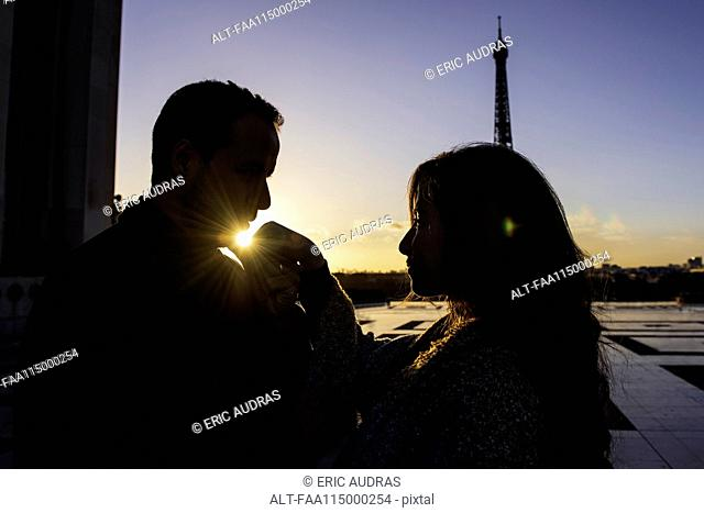 Man kissing his girlfriend near Eiffel Tower