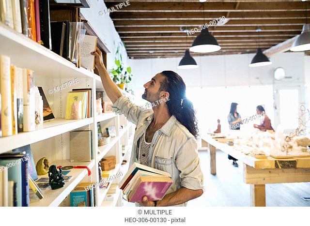 Male shop owner arranging books on bookshelf
