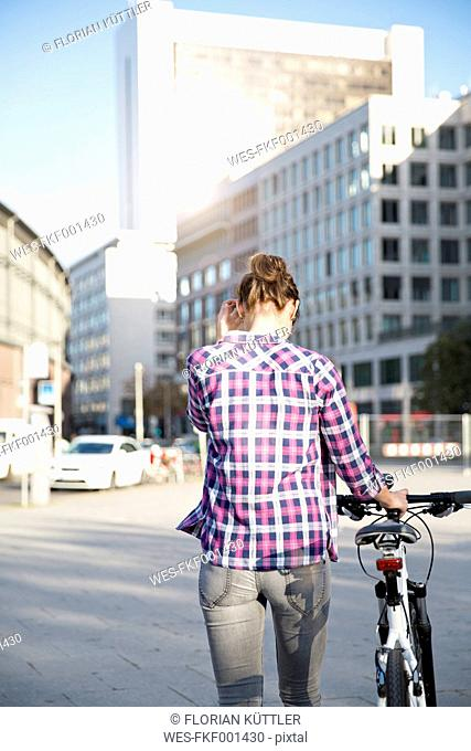Germany, Berlin, back view of young woman with bicycle