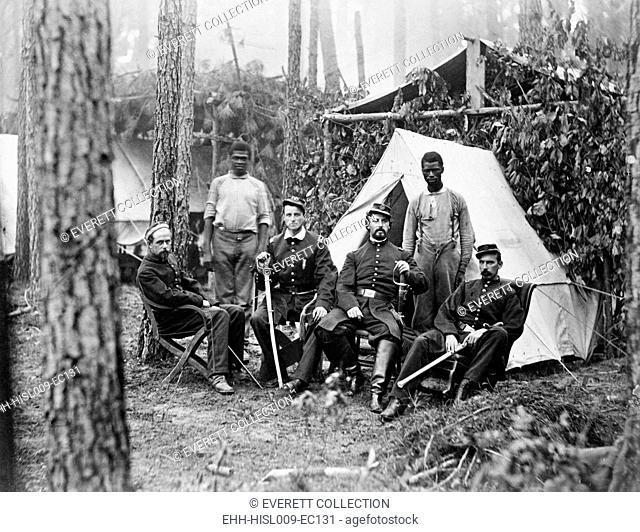 Four union officers in front of tent, with two Africans-American during the Petersburg Campaign of the last year of the war