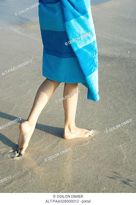 Child wrapped in towel walking on wet sand