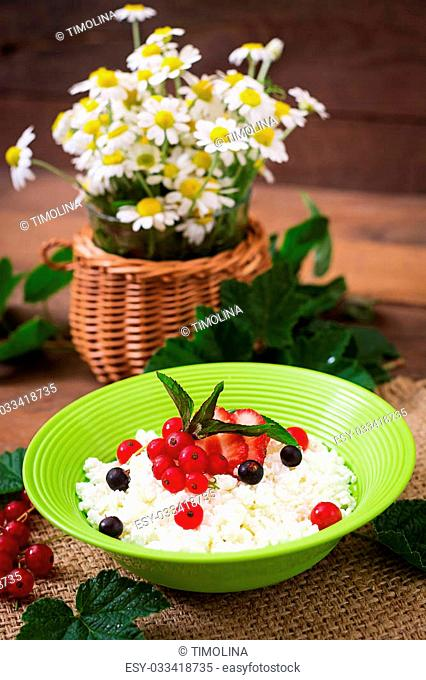 Cottage cheese for breakfast in green bowl on wooden background. Close up