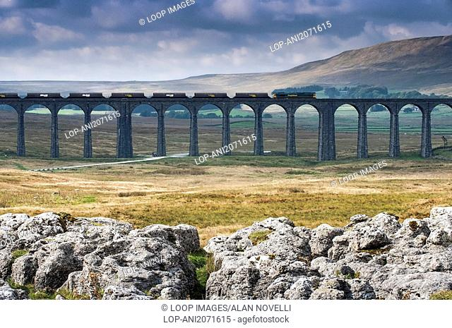 A train crossing the Ribblehead Viaduct backed by Whernside viewed from Runscar Scar limestone pavement