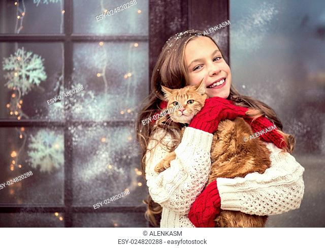 Child girl hugging her pet staying near her house decorated before Christmas