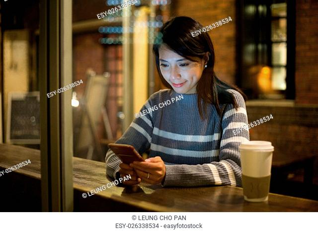 Woman use of mobile phone in cafe at night