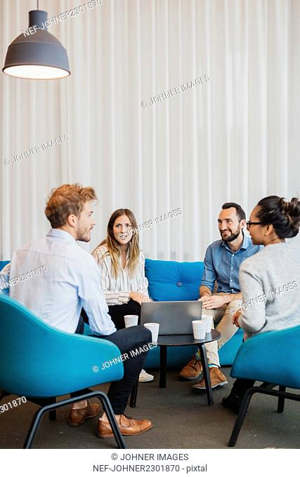 Four friends sitting in living room with laptop