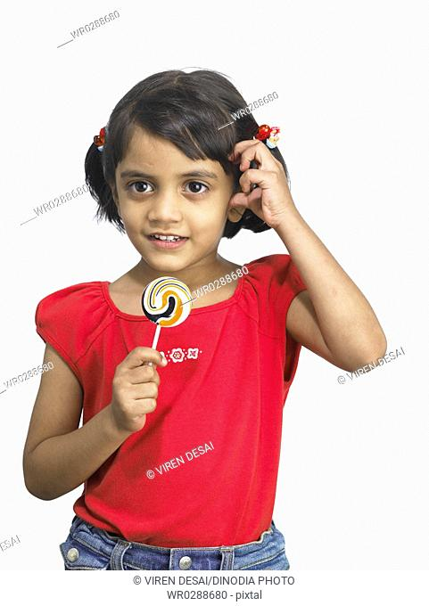 South Asian Indian girl holding lollipop in hand in nursery school MR