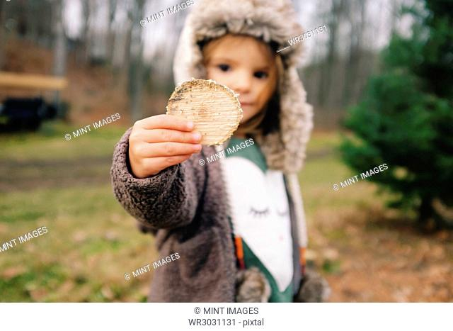 Young girl wearing furry hat standing outdoors, holding wooden disc towards camera