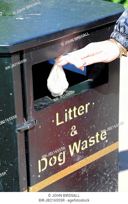 Putting dog dirt into a bin