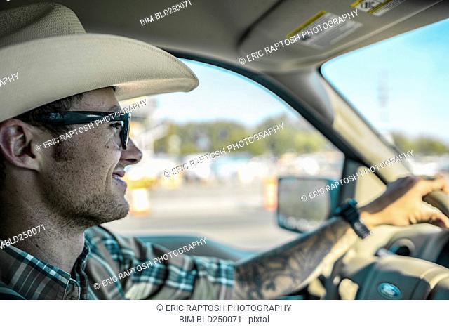 Caucasian man wearing cowboy hat driving car