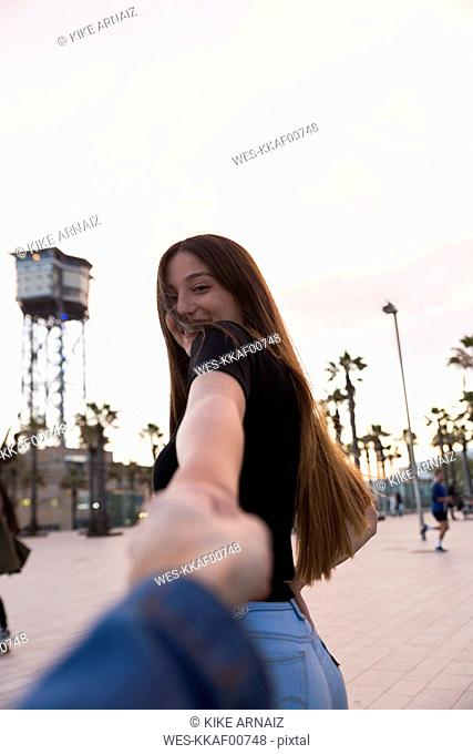 Spain, Barcelona, happy young woman holding hand