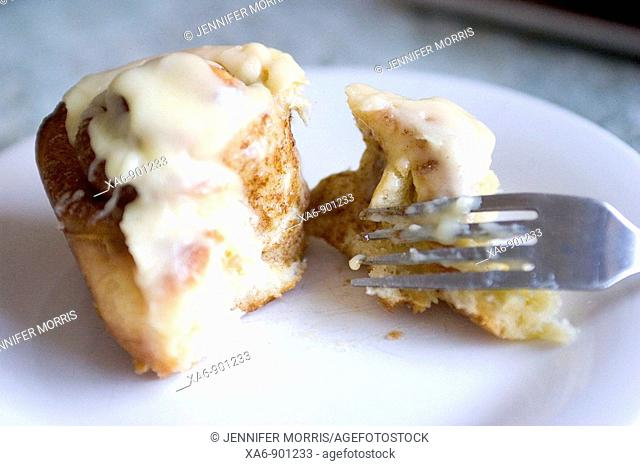 A warm, freshly-baked glazed cinnamon roll on a white plate with a fork