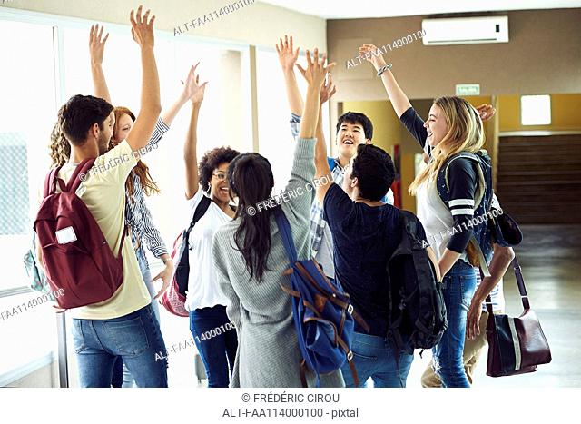 Group of students standing in a circle with hands raised in the air