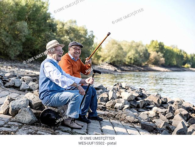 Two old friends sitting by the riverside, having fun
