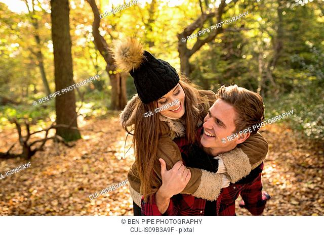 Young couple in forest, young man giving young woman piggyback, laughing