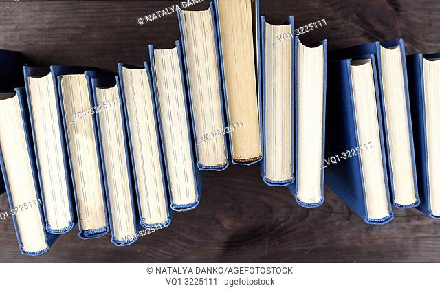stack of books in a blue cover on a brown wooden table, top view
