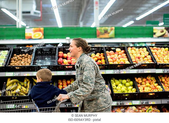 Female soldier and son in supermarket at air force military base