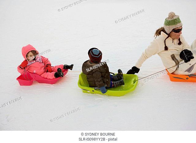 Mother pulling two children on sledges