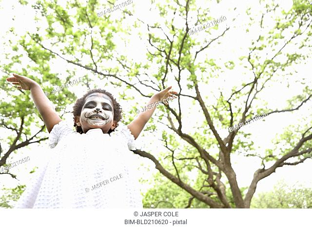 Black girl wearing face paint outdoors
