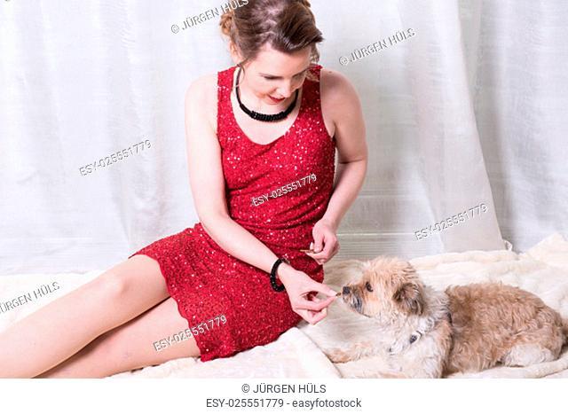 woman in red dress feeding dog on blanket