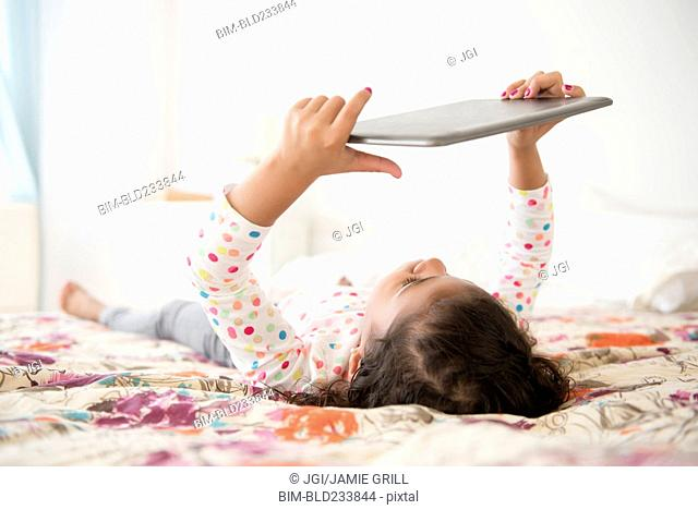 Mixed Race girl laying on bed using digital tablet