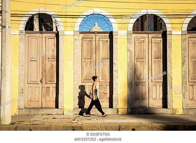 Brazil, Rio Grande do Sul, Praca General Osorio; Pelotas, Young woman walking on street