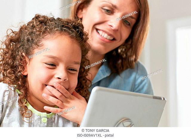Low angle view of mother and daughter using digital tablet, hand over mouth smiling