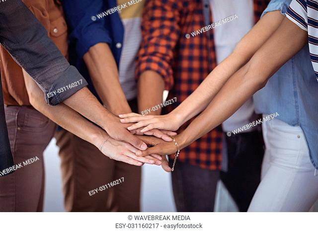 Mid section of business people stacking hands