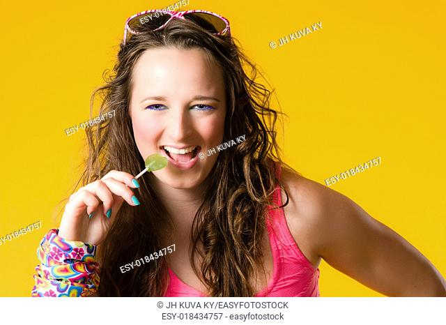 Close-up of beautiful girl and lollipop, make-up, yellow background
