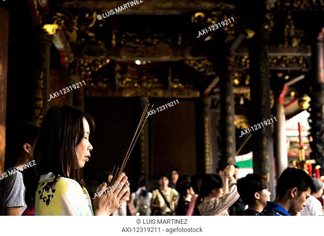 Buddhist Longshan temple in the city center of Taipei, people praying and burning incense; Taipei, Taiwan, China