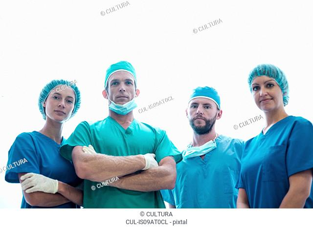 Portrait of four confident male and female surgeons wearing surgical scrubs