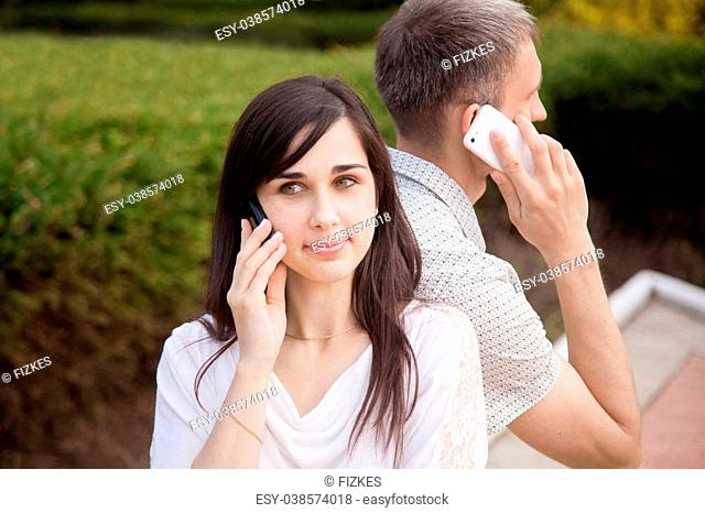 Young couple sitting back to back on park bench holding cell phones in hands, talking on mobile phones