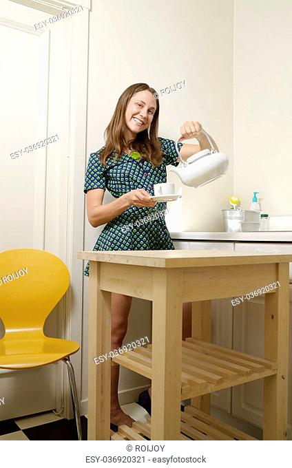 Young lady standing and pouring a cuppa