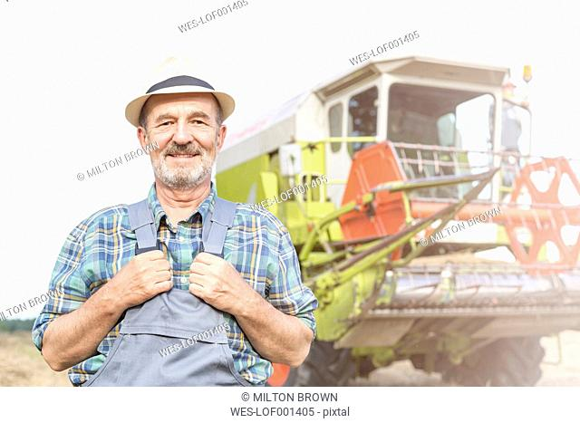 Confident farmer in front of combine harvester