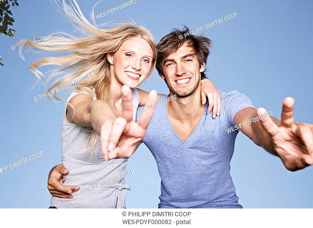 Germany, Cologne, Young couple showing peace sign, smiling, portrait