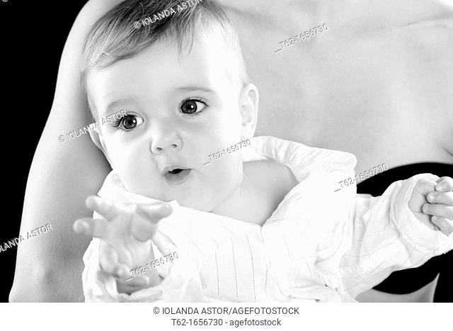 Smiling baby in the arms of his mother  Foreground  Black and White
