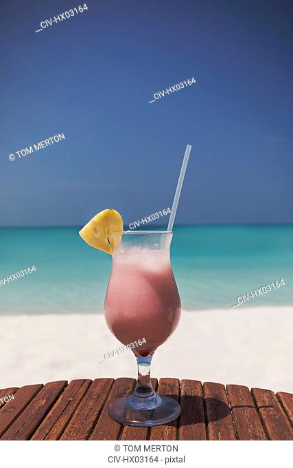 Pink cocktail with pineapple slice and straw on sunny tropical ocean beach
