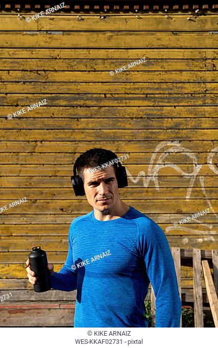 Athlete in front of wooden house with headphones and drinking bottle