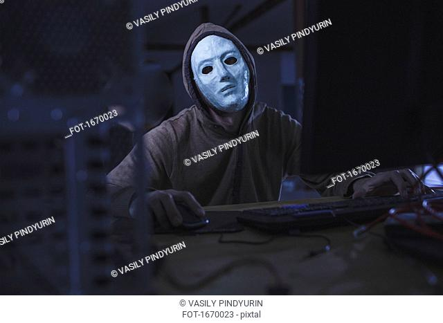 Computer hacker wearing mask and hood using computer while sitting at table