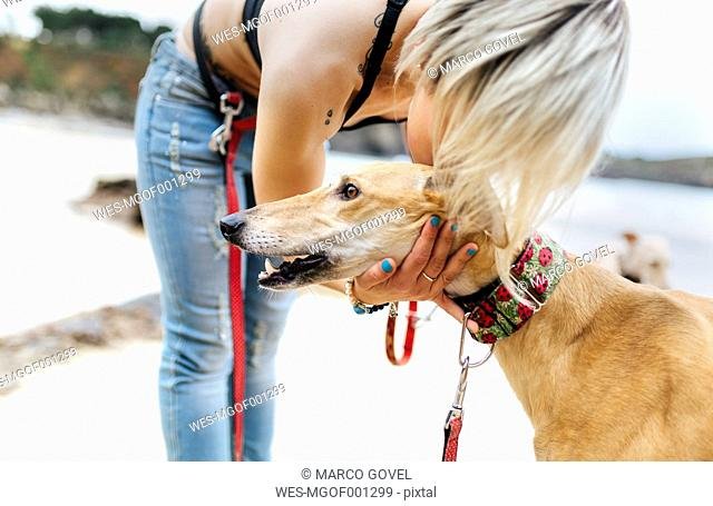 Spain, Llanes, young woman with her greyhound on the beach