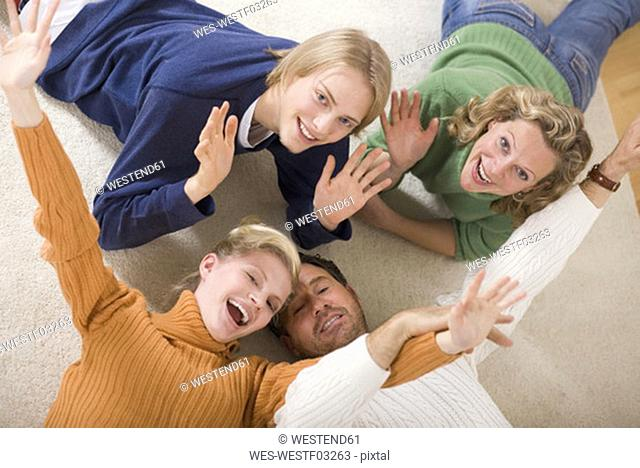 Family lying on floor in living room, smiling, elevated view