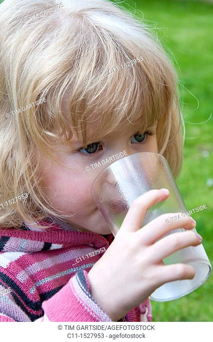 Young three year old girl drinking water