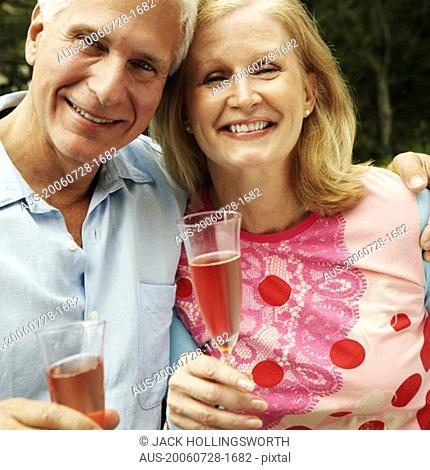 Portrait of a mature couple holding champagne flutes and smiling