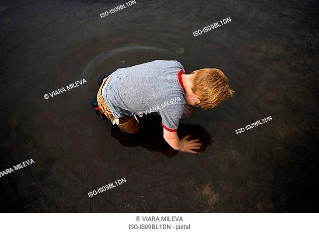 Boy kneeling in puddle on road