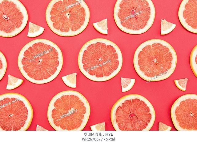 Cross sections of grapefruit against orange background
